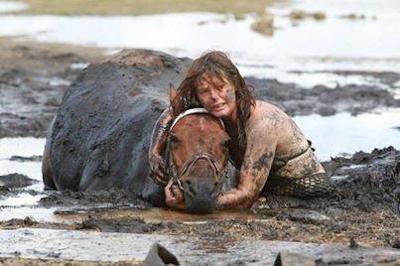 Una mujer ayuda a un caballo que se quedó atascado en el barro