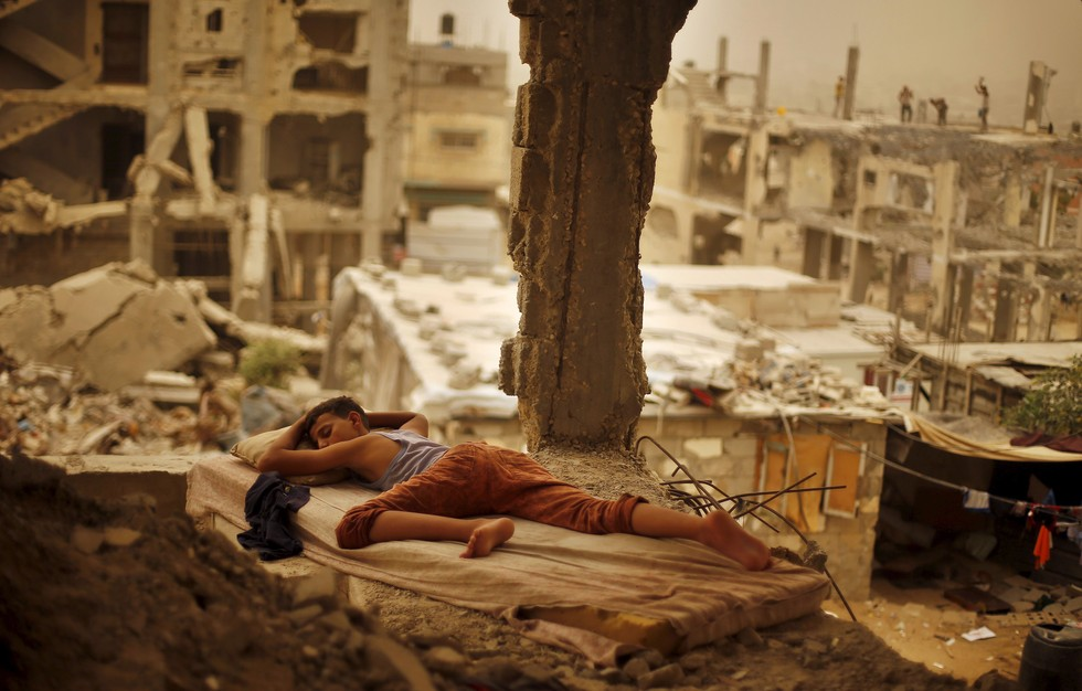 70 Of The Most Touching Photos Taken In 2015 - A Palestinian boy sleeps on a mattress inside the remains of his family's house. There has been increased violence between Palestine and Israel since September.