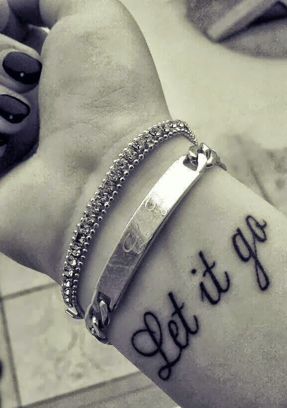 Let it go writing tattoo on wrist