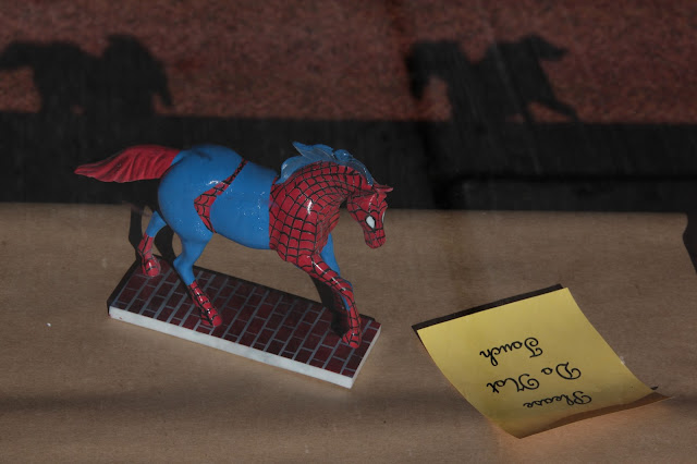 A horse figurine painted like Spiderman in a window display.