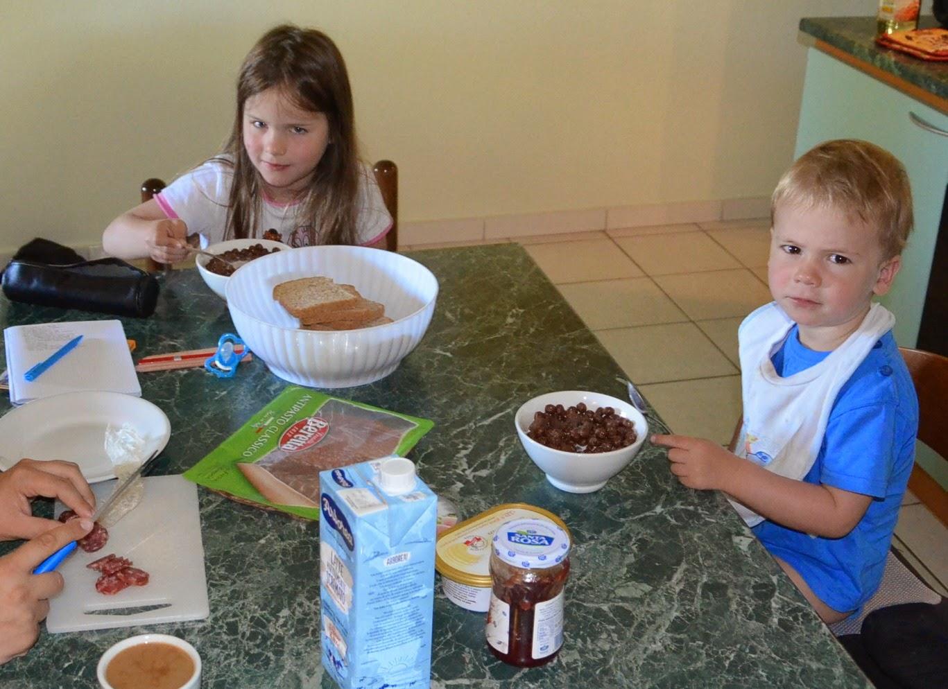 Kinder sitzen am Tisch und frühstücken
