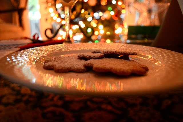 gingerbread cookies and eggnog with christmas tree lights in the background