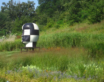 Black and white checkered giant head in a garden