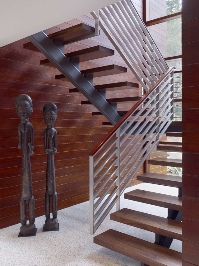 Steel and wood staircase with two statues