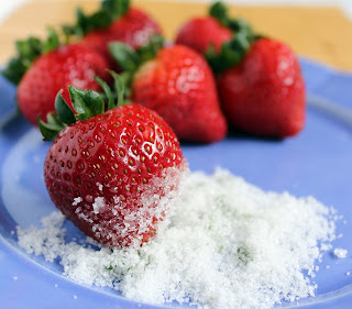 Blue plate containing several strawberries and basil sugar.