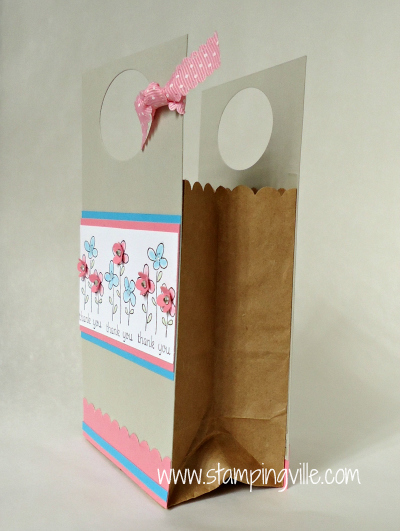 Small paper bag sandwiched between stamped and decorated card stock panels