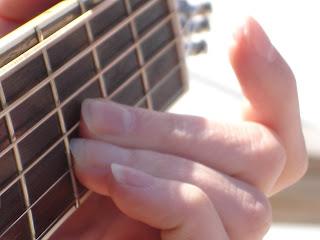Fingers, guitar fretboard, chord.