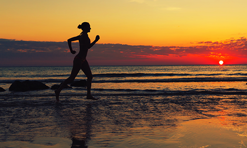 Girl running on beach in an effort to attain set goals.