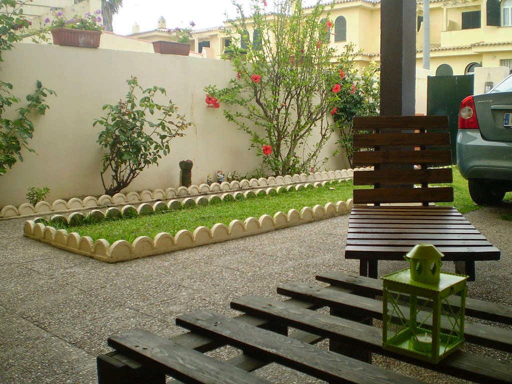 Zona de jardín con muebles hechos con maderas recicladas de palets.