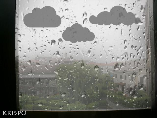 ventana con gotas de lluvia y nubes de papel pegadas a ella