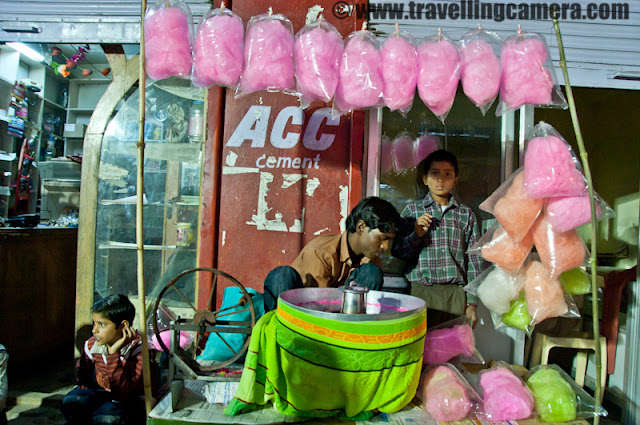 Mobilegiri at Famous Holi Mela of Ghuggar near Palampur in Himachal Pradesh : Posted by VJ SHARMA on www.travellingcamera.com : During Holi time I was in Dharmshala and planned a small trip to Palampur with one of my friend and got a chance to visit a popular Holi Mela in a small town called Ghuggar... Although I had never heard of this mela but after reaching Palampur many folks asked me to go there.. When I had to come back to Chandigarh, we had few hrs to spend around Palampur and planned a quick visit to Ghuggar to see what happens there... Here are few photographs clicked through Mobile Camera during a span of 15 minutes there.. Check out colors of Ghuggar, Palampur !!!Ram and Lakshman having wonderful ride on shoulders of Bajrangbali @ Ghuggar, Palampur , Himachal PradeshJust after parking our car, we headed towards the main market of Ghuggar, from where the Holi fair starts !!! Suddenly a huge crowd was moving towards us and we were worried about the time it would take to clear the road, as we had to o to Palampur back in next 20 minutes... We decided to park the car near other road  to minimize the risk :) After seeing this rally I was wondering how big this mela is going to be... by looking at the population of surrounding areas and crowd present in the fair, I concluded it as a huge mela which is difficult to imagine otherwise... Although my photographs would not be able to convey that... Lighting was not that good to use Mobile Camera in better way !!!Cute children dressed up as various characters and happy about the rath-yatra !!!Jalebi - Main sweet of most of the melas/Fairs in Himachal Pradesh... Jalebis and pakoras are two main things which can't be missed in these Melas and we also tried these !!!A Cute shopkeeper selling colors for upcoming Holi day !!!Bansuri, Glgoju, Siti and some other toys arranged around a stick.. These are one of the most popular toys among boys of any age.. Almost everyone had one of these and they were making huge noise in this Mela !!! At times it was irritating but itdoesn't matter after a particular point of time ...