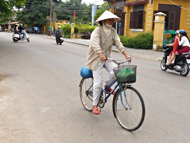 Vietnamese man on a bike wearing palm leaf hat