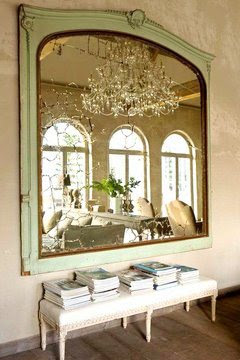 Large antique green mirror with a bench in a mansion in Belgium