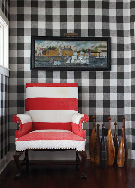 sitting area with black and white gingham walls, a wood floor and a red and white striped upholstered armchair with nail head details and decorative vintage bowling pins