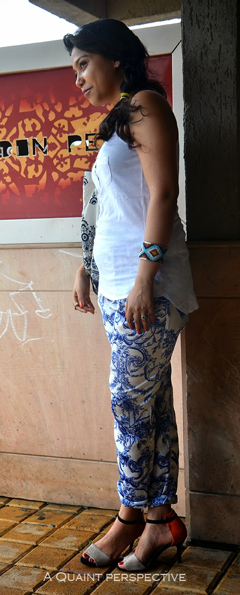 She wears a white comfortable sleeveless top with a pair of printed pants with Dutch blue-white pottery inspired wallpaper artwork