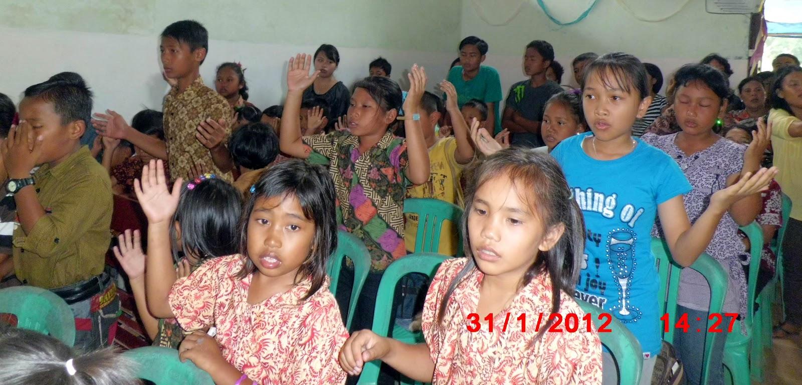 Anak-anak memuji Tuhan sambil mengangkat tangan