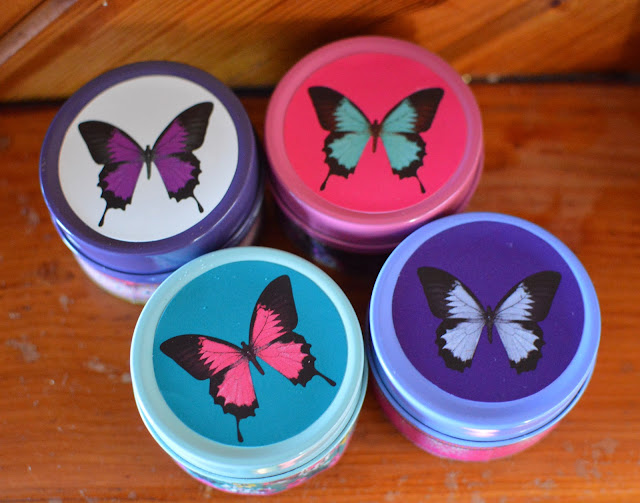 Four pretty butterfly print tin candles