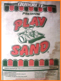 1 old, white bag of play sand with green and red accents.  Water stain off to the lower right side.