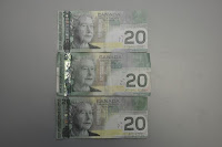 One real Canadian $20 bill between two fakes from Newfoundland.