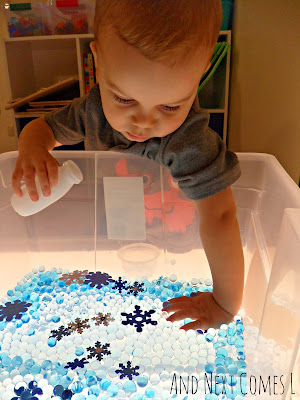 K checking out the winter sensory bin on the light table from And Next Comes L