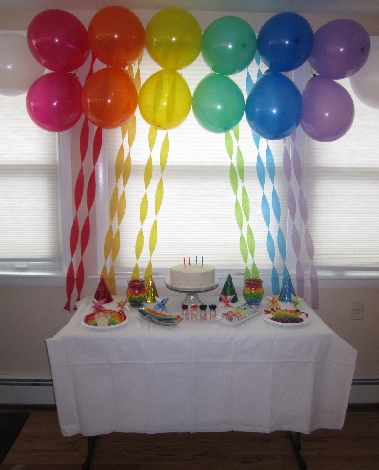 the display table with rainbow balloons and rainbow streamers