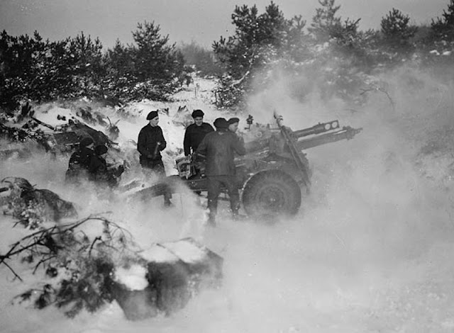 Gunners of the 2nd Heavy Anti-Aircraft Regiment, Royal Canadian Artillery, pushing a 3.7-inch (9.84 cm) anti-aircraft gun through mud. Dunkerque, France, February 1, 1945