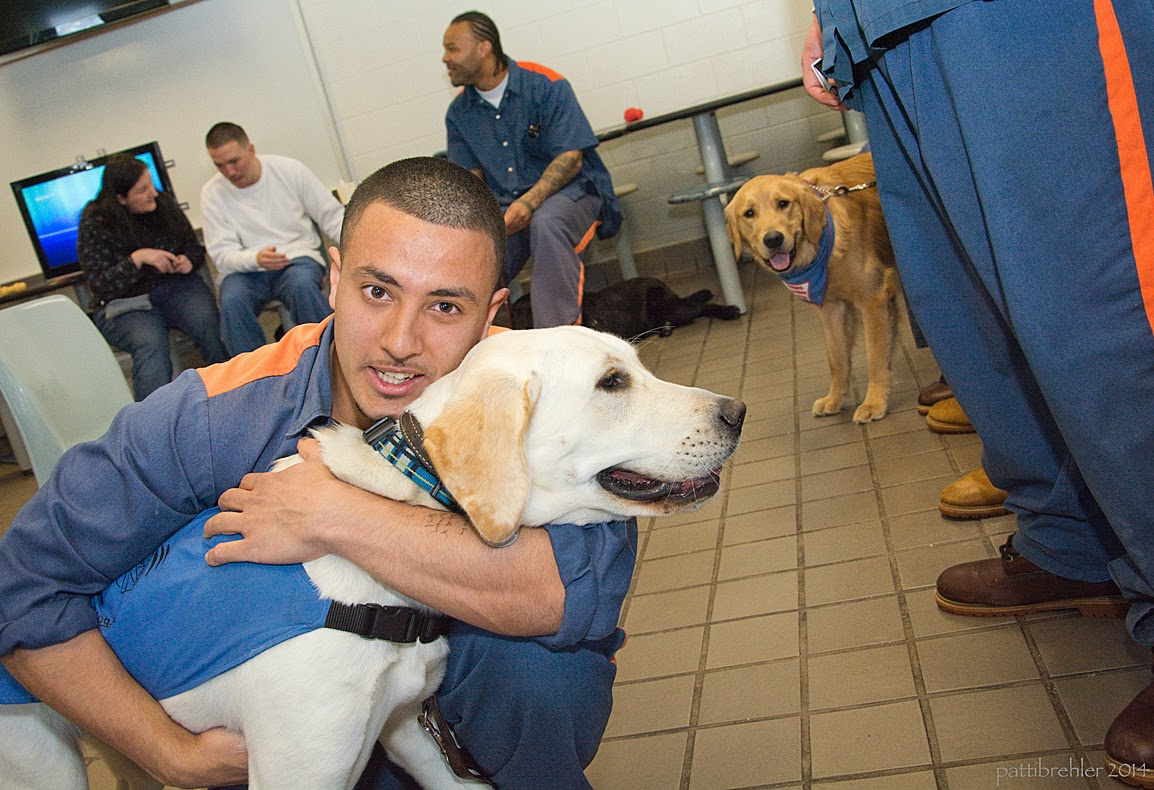 A man dressed in the blue prison uniform is squatting on a tile floor, he is hugging a young yellow lab. The lab is wearing a blue Future Leader Dog jacket. In the background are two men and a woman and a golden retriever, on the right side are the legs of men standing in a line.