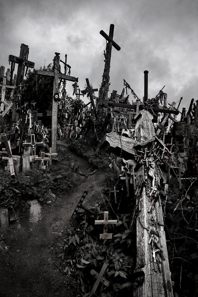 Imagem da Colina das Cruzes, ao alto e a preto e branco, apresentando um caminho ladeado por milhares de cruzes e uma ao cento, em cima, contra o céu nublado