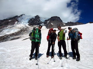 Team photo descending the Muir snowfield. Rainier with bad weather in the background.