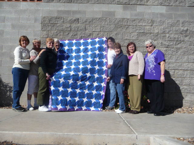 Group of Women Around Blue Houndstooth Quilt