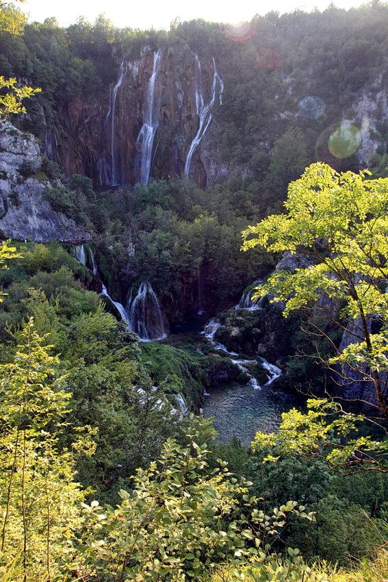 Paisagem das cascatas e lagos com o sol de frente e reflexos da lentes. Árvores muito iluminadas em primeiro plano