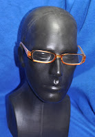 photo of orange reader glasses on a black plastic head