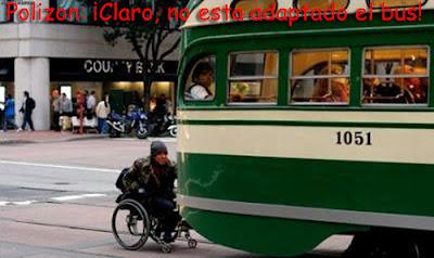 Una persona en sulla de ruedas se desplaza por la carretera cogido a la parte de atrás de un autobús. Cintenido del texto: Polizón: ¡Claro, no está adaptado el bus!
