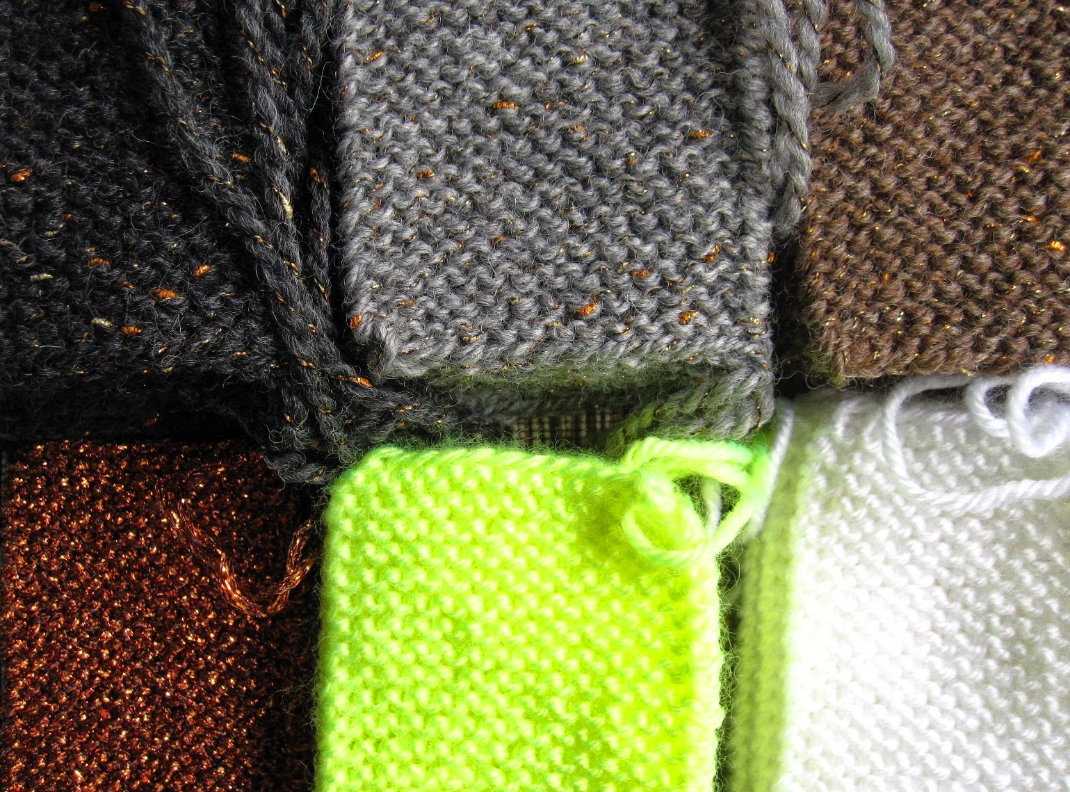 Rows of garter-stitch knitted rectangles in earth colours with shots of gold, and in bright white and neon yellow.