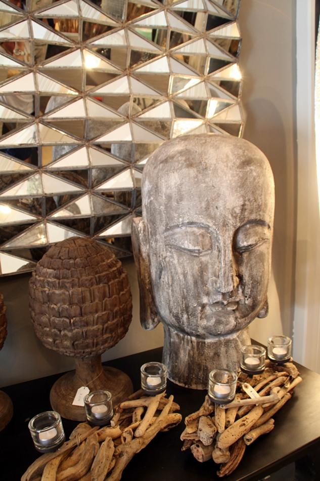 Buddha Kopf auf einer Kommode mit hölzernen Teelichtern