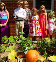children stand in a row behind a wildly growing garden with large pumpkin in foreground