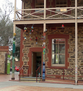 The door to the exhibition is decorated with yarn bombs on the verandah posts and hanging from the balcony above.