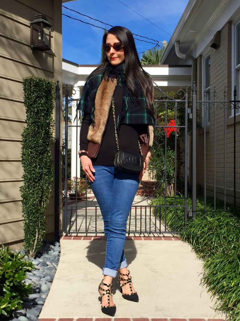 Facing forward with sunglasses on and faux fur vest and plaid scarf.