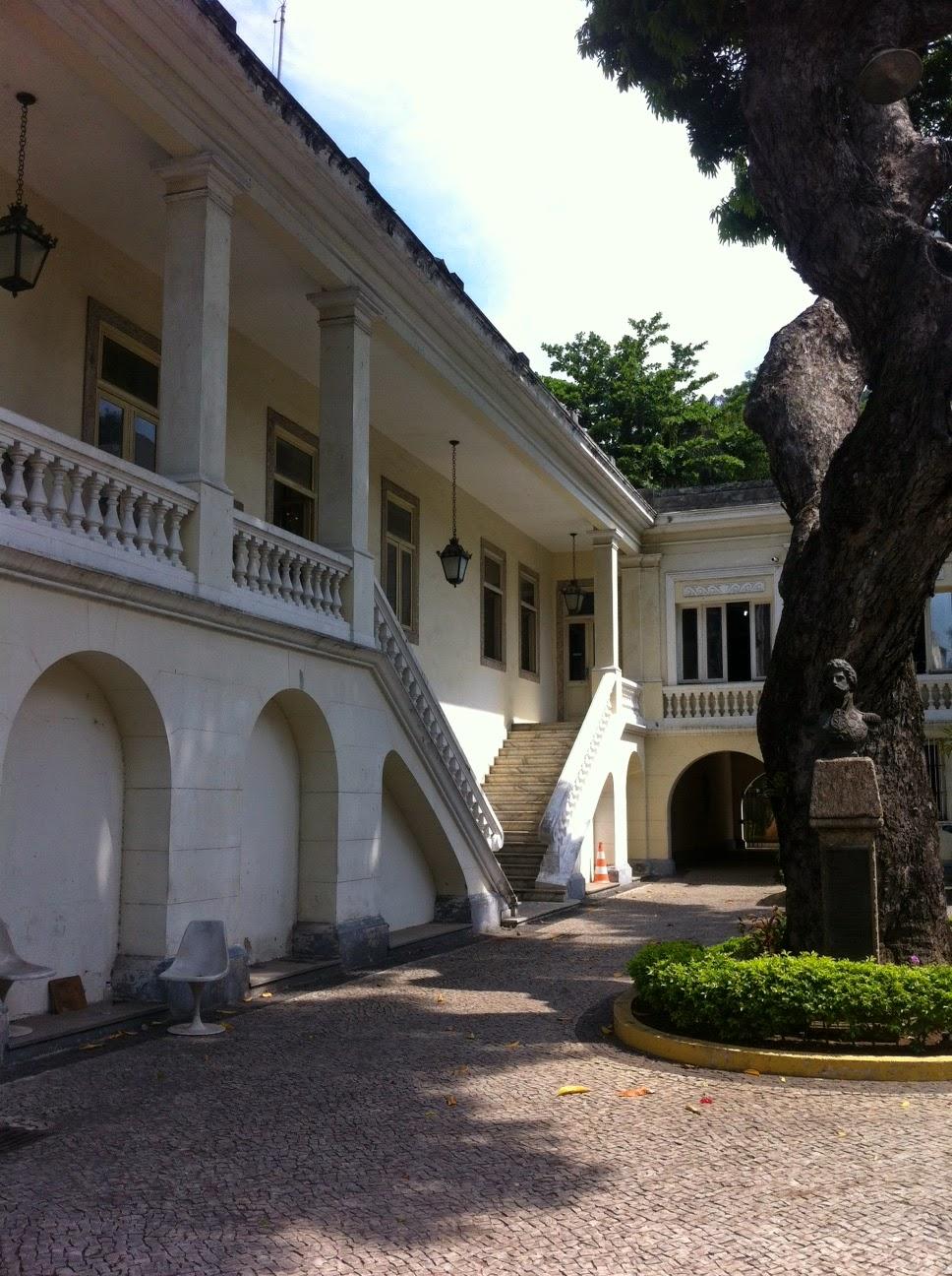 Descrição da Foto: Fachada externa da entrada do museu. Um grande sobrado branco com duas escadas que se encontram no térreo. Ele está ao lado esquerdo e no fundo, enquanto ao lado direito o tronco de uma frondosa árvore.