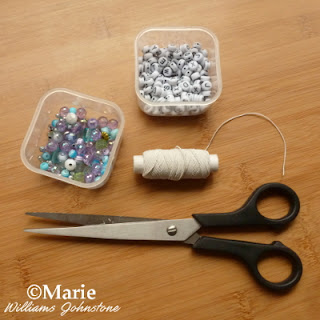 Scissors, beads, alphabet beads and elastic