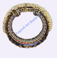 Bangle, Rajasthan, 19th cent. AD  In this classic combination of enamels and gems, the bangle (one of a pair) has part of its outer surface set with diamonds and rubies. The front is frilled with seed pearls held on gold wire, whereas the inner surface is rich with red and green enamelling on a white base.