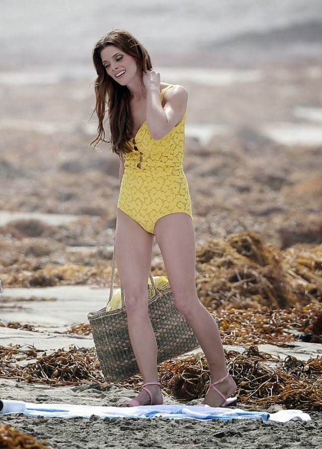 Ashley Greene on set filming beach scenes in a yellow swimsuit