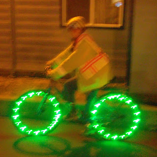 Cynthia M. Parkhill wearing yellow-green bike helmet, rain jacket and vest atop her bicycle at night. MicroLED lights form green circles of light along the rims of her tires.