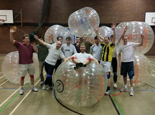 Men in a sports hall standing by bubble football suits / Zorb Football Suits