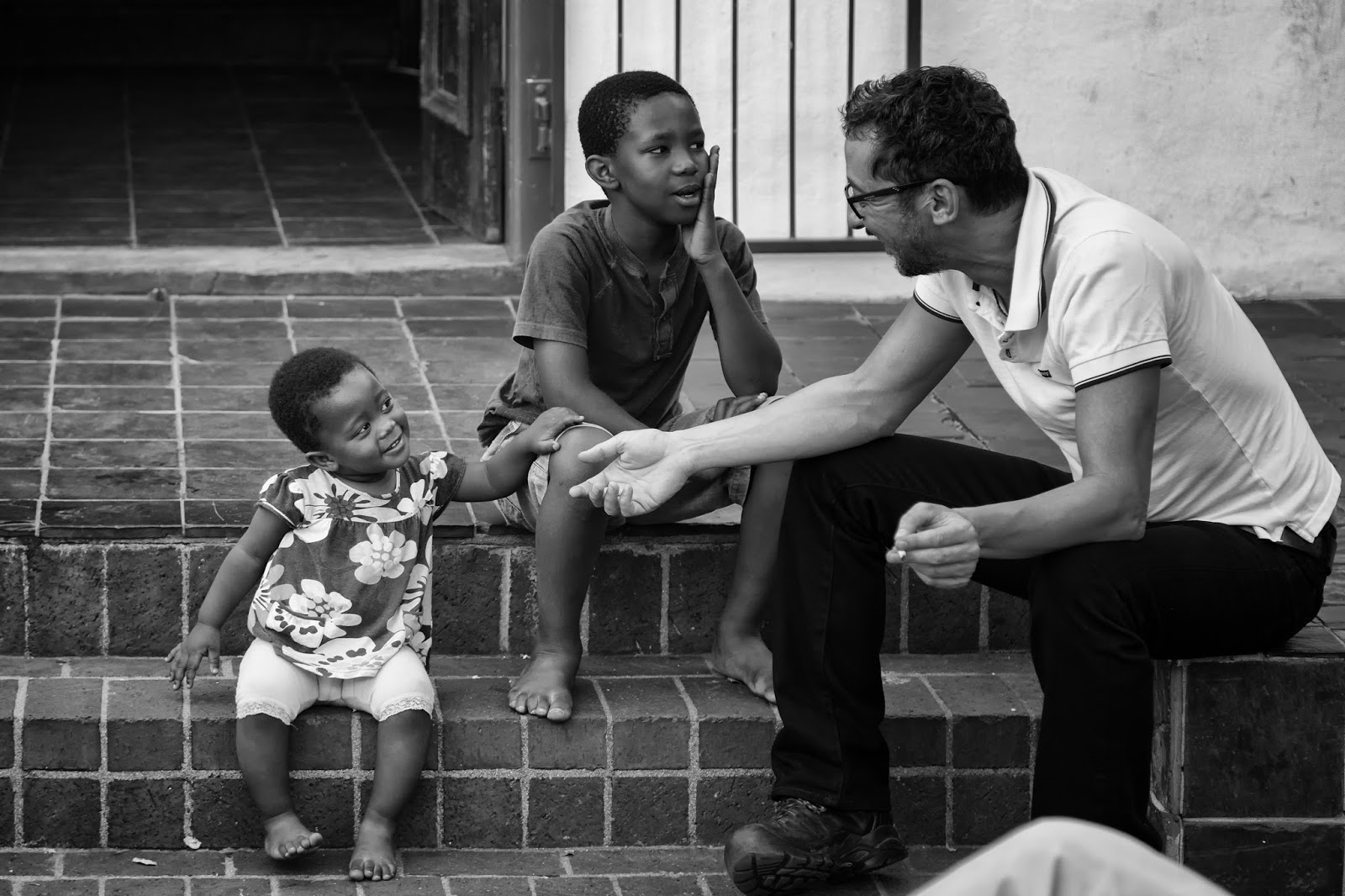 A little girl smiles coyly at a man while her brother looks on.