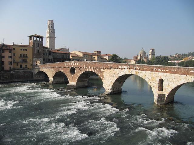 Brücke von der innenstadt zum castel del pietro im hintergrund links