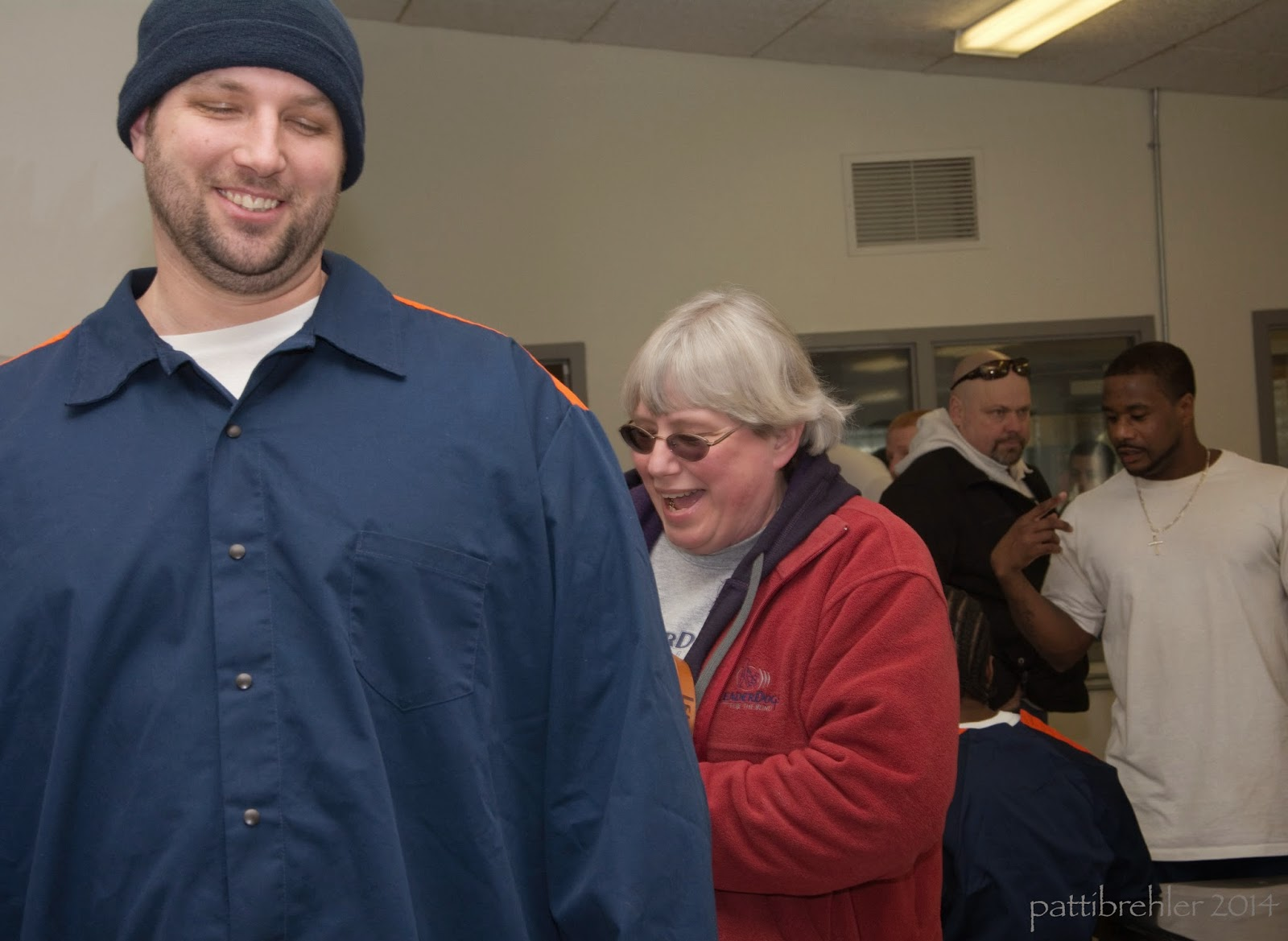 A tall man wearing a dark blue long sleeved shirt and a blue knit cap is facing the camera on the left side. He is smiling and his eyes are closed. To the right behind him is a shorter woman with short white hair and glasses, she is wearing a red fleece jacket. She is holding something behind the man's back out of view and is looking at it, it appears she is laughing. In the far background are two men standing, one is african american and is wearing a white t-shirt, the other man is bald and has sunglasses on the top of his head and is wearing a black jacket.