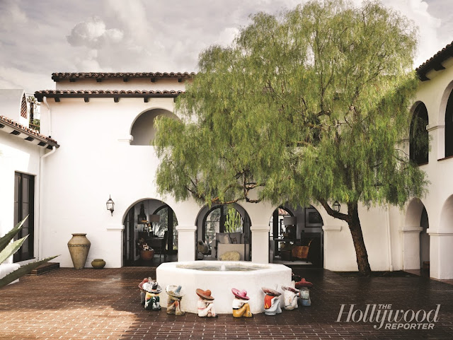 interior courtyard of a Spanish Colonial Revival home with a fountain and willow tree