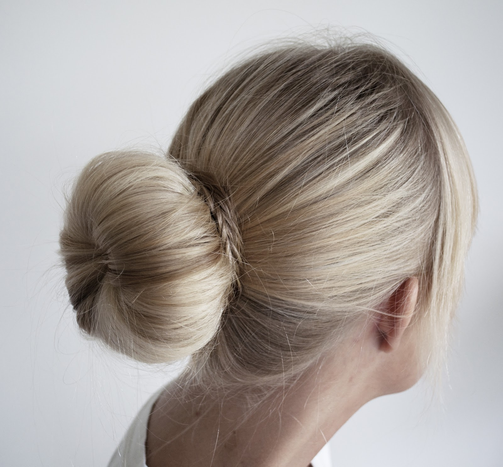 Instead of adding big, loose curls to your medium-length or long tresses, upgrade your party look with a big bun hairstyle instead. With a little effort and a soft doughnut ring, you can transform a ponytail into the chicest chignon at the nape or a voluminous ballerina bun worn on the top of your head.