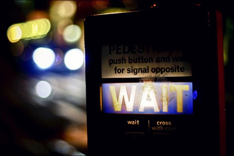 Pelican Crossing at Night time. Illuminated sign reads WAIT. Pedestrians push button and wait for signal opposite.